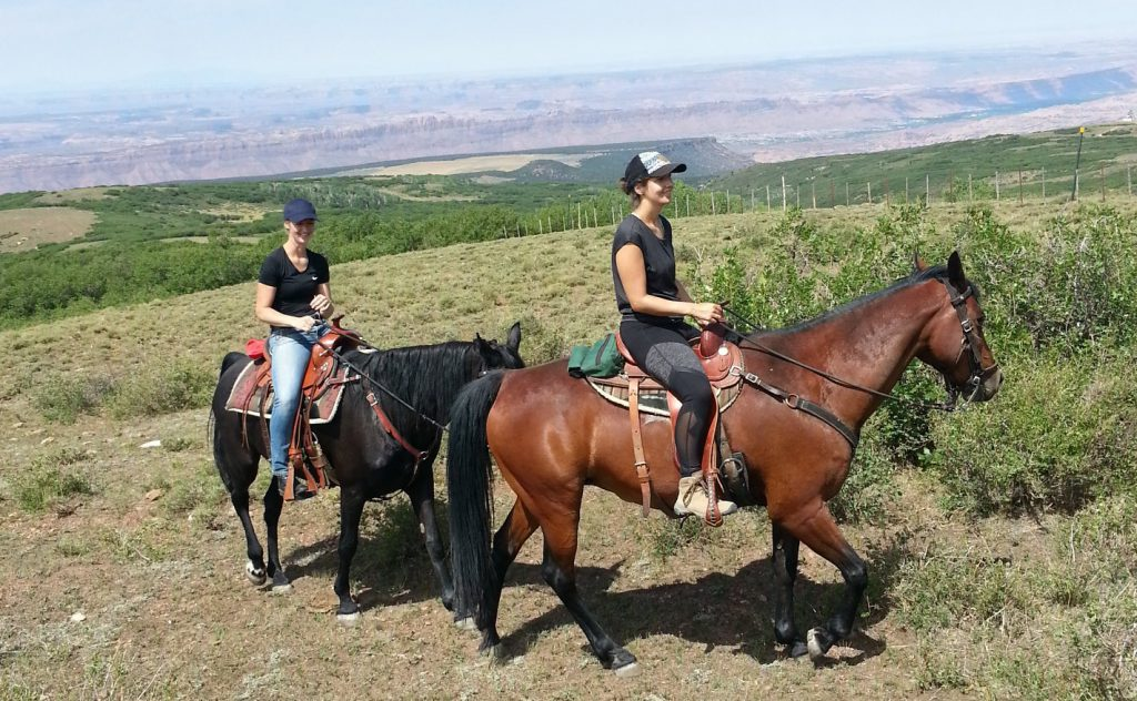 Two young women ride high above the red rock desert.
